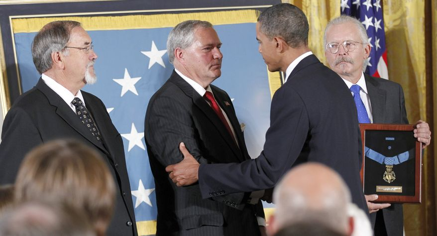 President Obama presents the Medal of Honor to the sons of the late Air Force Chief Master Sgt. Richard L. Etchberger -- (from left) Richard Etchberger, Corey Etchberger and Steve Wilson -- on Tuesday, Sept. 21, 2010, during a ceremony in the East Room of the White House in Washington.  (AP Photo/Pablo Martinez Monsivais)