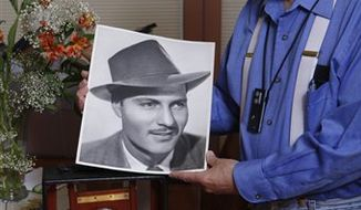This May 18, 2010 photo shows historian Loren Latker posing with his collection of photographic memorabilia of Los Angeles' Raymond Chandler at his home in the Marina del Rey area of Los Angeles. Chandler wanted to be buried next to his beloved wife, Cissy. That they would end up about a block apart, one in a cemetery, the other on a mausoleum warehouse shelf, is a tale with many twists. But thanks to a court order this month, expect a very un-Chandler-like happy ending. The two will be reunited during a scheduled celebration next Valentine's Day at the writer's grave in San Diego's Mount Hope Cemetery. (AP Photo/Damian Dovarganes)
