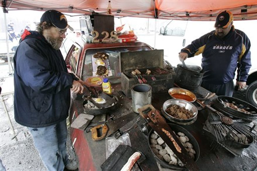 FILE - This Jan. 1, 2008, file photo shows Ken Johnson, left, and an unidentified assistant cooking food on the hood of his car while tailgating at the Winter Classic at Ralph Wilson Stadium in Orchard Park, N.Y. No longer feeling welcome in the main parking lot, Ken Johnson is taking his popular NFL football tailgating party elsewhere after spending the past 14 years in the same spot. (AP Photo/David Duprey, File)