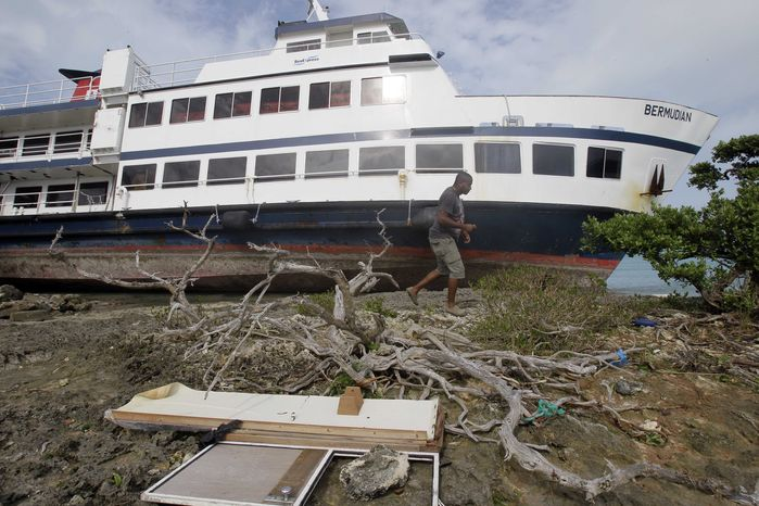 """A man walks by the excursion boat """"Bermudian"""" after it broke loose and was pushed to shore by Hurricane Igor in St. George, Bermuda, Monday, Sept. 20, 2010. (AP Photo/Gerry Broome)"""