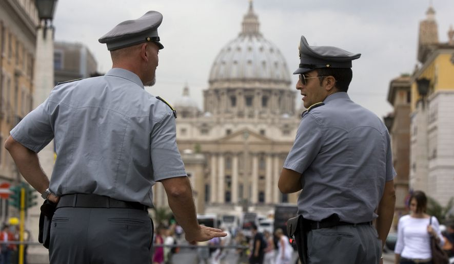 Italian financial police officers talk with each other in front of St. Peter's Square at the Vatican on Tuesday, Sept. 21, 2010. Italian authorities have seized 23 million euros ($30.18 million) from a Vatican bank account and begun investigating top officials of the bank in connection with a money-laundering probe. (AP Photo/Angelo Carconi)