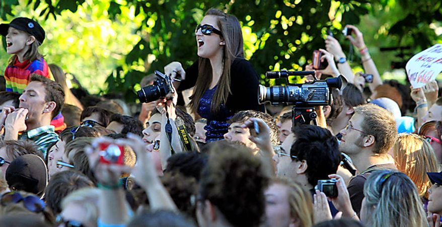 """Members of the crowd react to recording artist Lady Gaga as she speaks at a rally in support of repealing the military's """"don't ask, don't tell"""" policy for gay service members, in Portland, Maine, on Monday, Sept. 20, 2010. (AP Photo/Pat Wellenbach)"""
