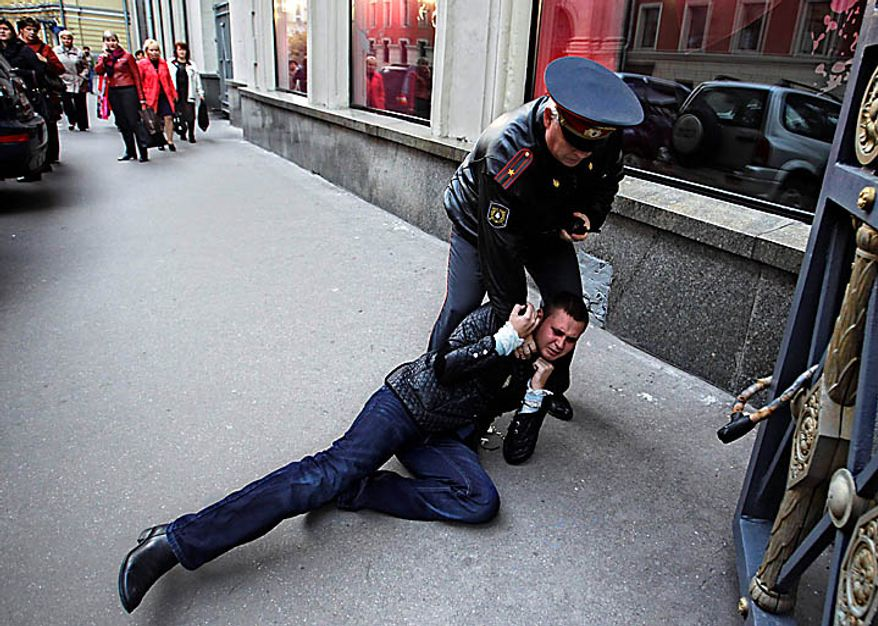 "Police officer detains a gay rights activist during a rally near city hall in Moscow, Tuesday, Sept., 21, 2010. Moscow police has dispersed a gay rally and detained activists protesting homophobic policies of Moscow authorities. Mayor Yuri Luzhkov has called homosexuals ""satanic"" and routinely thwarted their attempts to hold a gay pride in Moscow. Police officers detained on Tuesday at least a dozen activists in a Moscow square near the city hall minutes after they brought out a papier-mache mummy that resembled Luzhkov and unfurled posters ridiculing him. (AP Photo/Sergey Ponomarev)"
