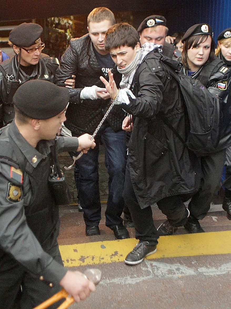 Police officers detain Russian gay rights activist Nikolai Alexeyev during a rally near city hall in Moscow, Tuesday, Sept. 21, 2010. Moscow police has dispersed a gay rally and detained activists protesting homophobic policies of Moscow authorities. (AP Photo/Mikhail Metzel)