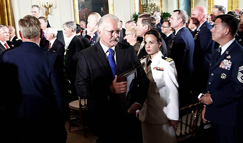 Richard Etchberger, center, carries his father's, Air Force Chief Master Sgt. Richard L. Etchberger, Medal of Honor that was present posthumously by President Barack Obama, following a ceremony in the East Room of the White House in Washington, Tuesday, Sept. 21, 2010. Etchberger received the honor for his heroic actions in combat in Laos on March 11, 1968, after deliberately exposing himself to enemy fire in order to put his wounded comrades in rescue slings permitting them to be airlifted to safety. (AP Photo/Pablo Martinez Monsivais)