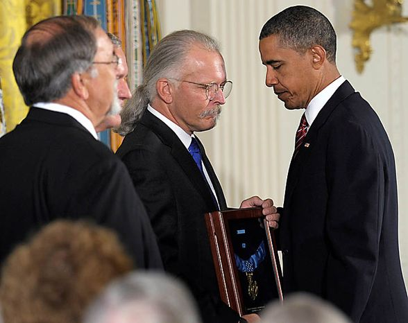 President Barack Obama presents the Medal of Honor posthumously to the sons of Air Force Chief Master Sgt. Richard L. Etchberger, from right, Richard Etchberger, Corey Etchberger, and step son Steve Wilson , Tuesday, Sept. 21, 2010, during a ceremony in the East Room of the White House in Washington. Etchberger received the honor for his heroic actions in combat in Laos on March 11, 1968, after deliberately exposing himself to enemy fire in order to put his wounded comrades in rescue slings permitting them to be airlifted to safety. (AP Photo/Susan Walsh)