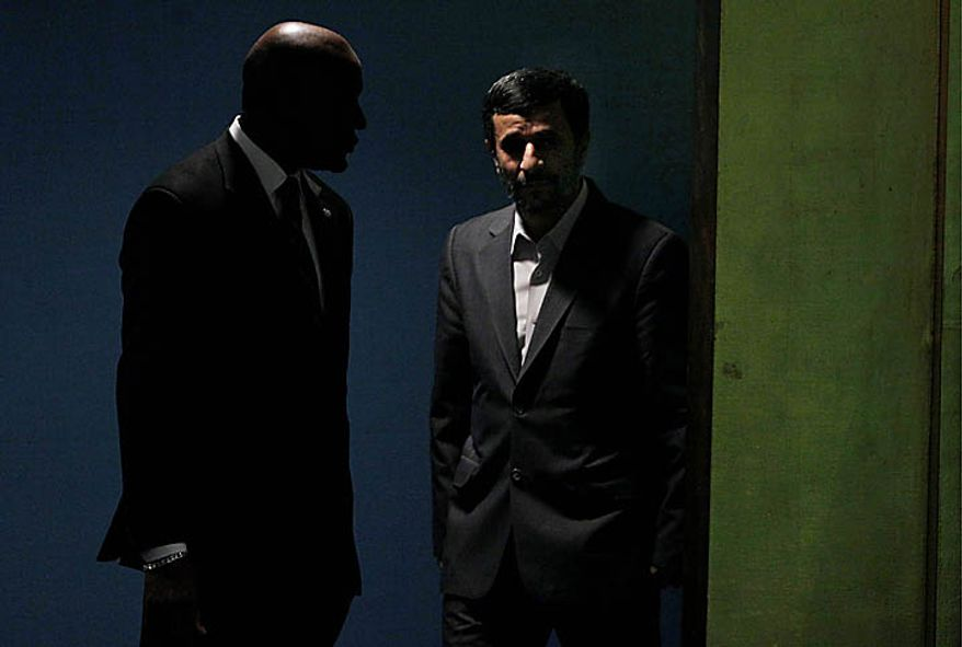 Mahmoud Ahmadinejad, right, President of Iran, is escorted to the podium to address a summit on the Millennium Development Goals at United Nations headquarters onTuesday, Sept. 21, 2010. (AP Photo/Richard Drew)