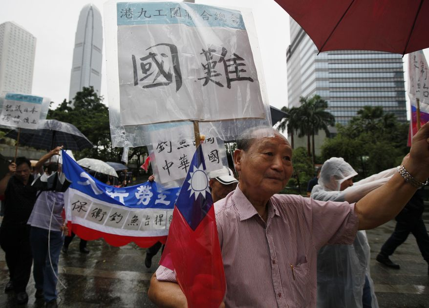 "Taiwanese veteran soldiers and anti-Japan protesters hold banners that read ""National Crisis"" (top) and ""Protect Diaoyu Islands"" during a demonstration in Hong Kong on Tuesday, Sept. 21, 2010. (AP Photo/Kin Cheung)"