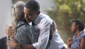 President Obama hugs a guest Wednesday after listening to her story in the backyard of a private residence in Falls Church, Va., where Obama discussed the Patient's Bill of Rights and health care reform. (Associated Press)