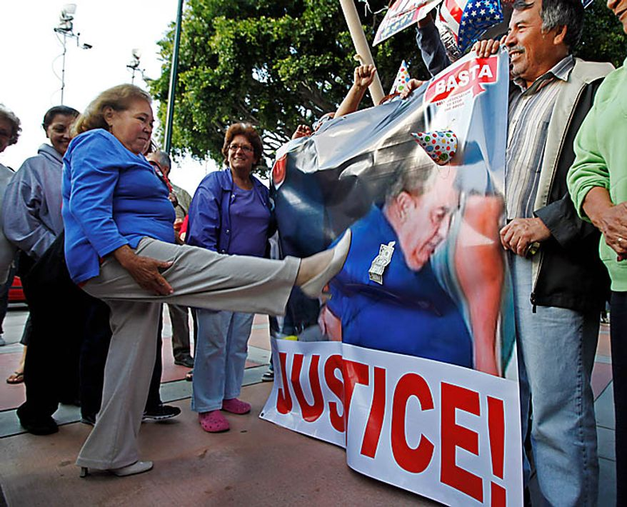 A woman aims a kick at an image of former City Manager Robert Rizzo, made during his arrest early Tuesday at his Huntington Beach home, as residents of the city of Bell, Calif., celebrate the arrest of current and former city officials on corruption charges, outside City Hall Tuesday, Sept. 21, 2010.  (AP Photo/Reed Saxon)