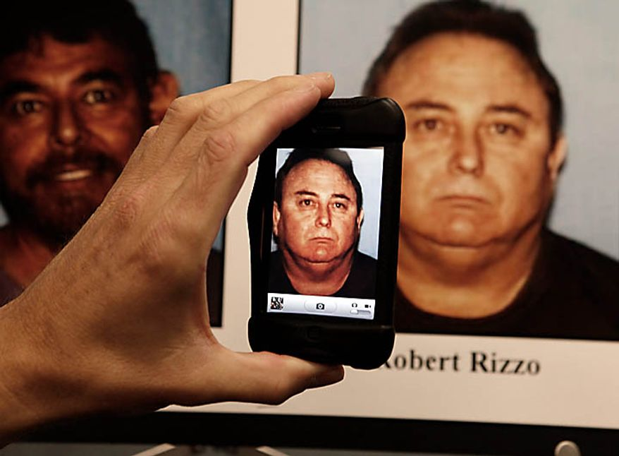 A member of the media uses a telephone to take a picture of a mug shot of Bell, Calif.'s former city manager, Robert Rizzo who was arrested Tuesday Sept. 21, 2010 and displayed during a district attorney news conference in Los Angeles. Rizzo and seven other city officials were arrested over allegations of corruption, misuse of public funds and voter fraud. (AP Photo/Nick Ut)