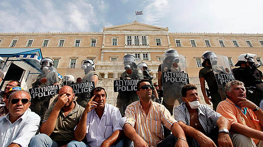 Truck drivers sit in front of a riot police cordon during a protest outside the Greek Parliament in Athens, Wednesday, Sept. 22, 2010. Truckers strongly oppose government plans to reform their sector and abolish strict licensing rules. (AP Photo/Evi Zoupanou)