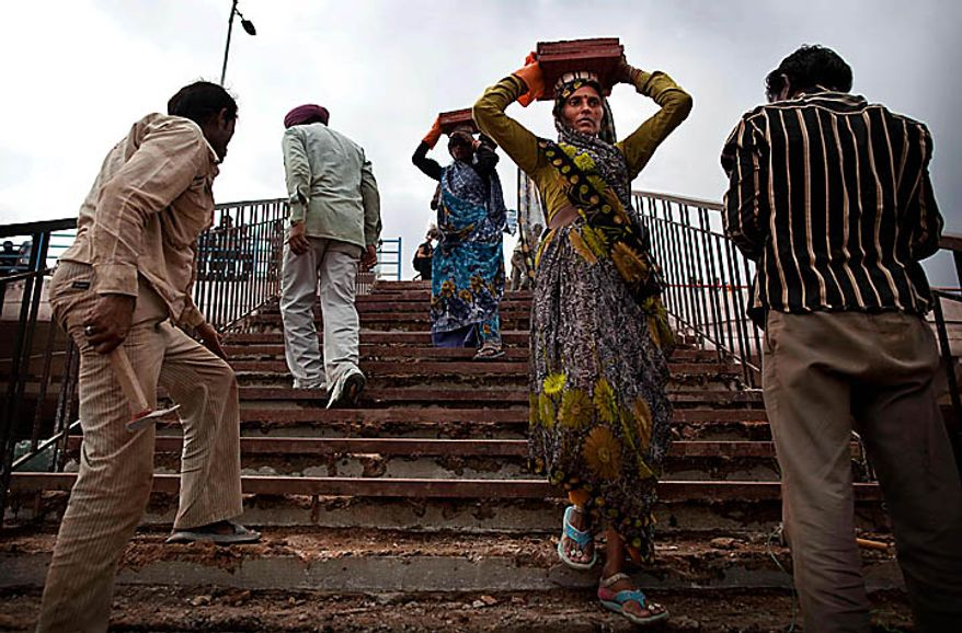 """Indian laborers carry bricks near the scene where a bridge collapsed Tuesday, outside Jawaharlal  Nehru Stadium, the main venue for the Commonwealth Games, in New Delhi, India, Wednesday, Sept. 22, 2010. The Commonwealth Games chief rushed to New Delhi seeking emergency talks with the prime minister over India's chaotic preparations, as two world champion competitors withdrew and England warned that problems with the athletes' village have left the sporting event on a """"knife-edge."""" Indian officials insisted that facilities would be ready and immaculate for the Oct. 3 games opening despite wide-ranging concerns about unfinished buildings construction collapses and an outbreak of dengue fever. (AP Photo/Kevin Frayer)"""