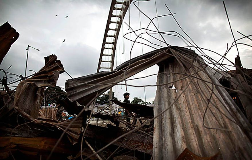 "An Indian laborer is seen through debris near the area where a bridge collapsed Tuesday, outside Jawaharlal Nehru Stadium, the main venue for the Commonwealth Games,in New Delhi, India, Wednesday, Sept. 22, 2010.  The Commonwealth Games chief rushed to New Delhi seeking emergency talks with the prime minister over India's chaotic preparations, as two world champion competitors withdrew and England warned that problems with the athletes' village have left the sporting event on a ""knife-edge."" Indian officials insisted that facilities would be ready and immaculate for the Oct. 3 games opening despite wide-ranging concerns about unfinished buildings construction collapses and an outbreak of dengue fever. (AP Photo/Kevin Frayer)"
