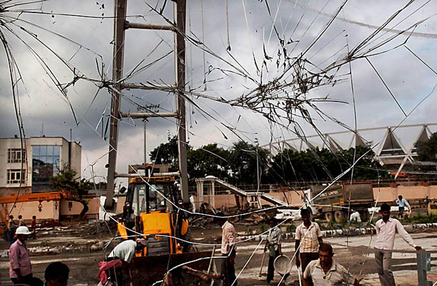 Indian laborers are seen through the damaged window of a bulldozer at the scene where a bridge collapsed Tuesday, near Jawaharlal Nehru Stadium, the main venue for the Commonwealth Games, in New Delhi, India, Wednesday, Sept. 22, 2010. (AP Photo/Kevin Frayer)