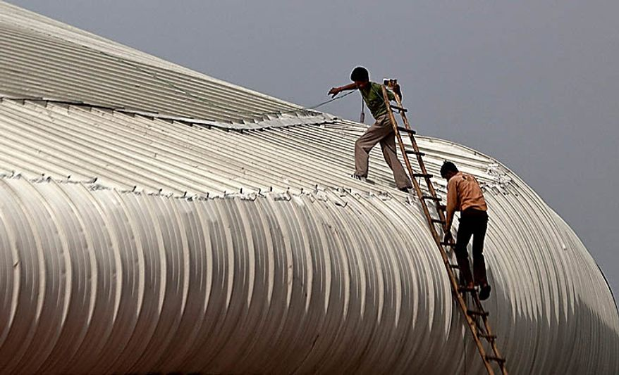 """Indian laborers walk on the roof of the weightlifting venue near Jawaharlal Nehru Stadium, the main venue for the Commonwealth Games, following an incident with the interior ceiling in New Delhi, India, Wednesday, Sept. 22, 2010. The Commonwealth Games chief rushed to New Delhi seeking emergency talks with the prime minister over India's chaotic preparations, as two world champion competitors withdrew and England warned that problems with the athletes' village have left the sporting event on a """"knife-edge."""" Indian officials insisted that facilities would be ready and immaculate for the Oct. 3 games opening despite wide-ranging concerns about unfinished buildings construction collapses and an outbreak of dengue fever.  (AP Photo/Kevin Frayer)"""