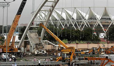 A crane lifts debris from a pedestrian bridge that collapsed Tuesday outside the Jawaharlal Nehru Stadium, the main venue for the Commonwealth Games, in New Delhi, India, Wednesday, Sept. 22, 2010. Top Indian officials dismissed international anger over the pedestrian bridge collapse and the revelation that sports officials arrived to find filth in the athlete's village, news reports said Tuesday. The statements come as some athletes announced they would not attend the Commonwealth Games, and international sports officials warned their countries may be forced to withdraw amid a frenzy of last-minute preparations. (AP Photo/Manish Swarup)