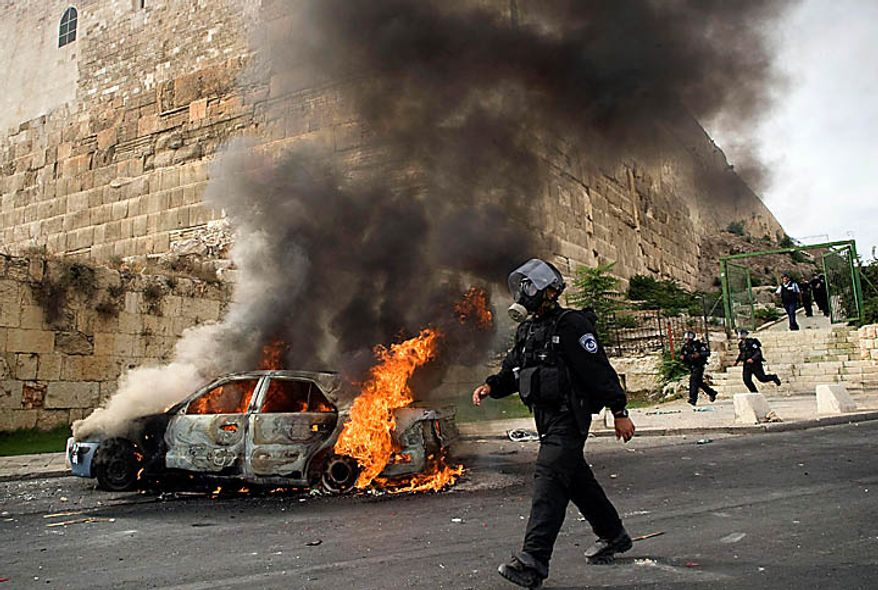 An Israeli police officer wearing a gas mask walks past a car set on fire by Palestinian rioters during clashes outside Jerusalem's Old City, Wednesday, Sept. 22, 2010. Violence erupted after a 32-year-old Palestinian laborer was killed by a private security guard watching over Jewish families in the Silwan neighborhood in east Jerusalem. During the man's funeral, a mob of protesters set tires on fire, smashed the windows of several buses and called for revenge.  (AP Photo/Sebastian Scheiner)