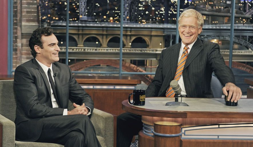 "In this photo released by CBS, actor Joaquin Phoenix, left, joins host David Letterman on the set of the ""Late Show with David Letterman,"" Wednesday, Sept. 22, 2010, in New York. This is Phoenix's first television appearance and first visit to the CBS broadcast since February 2009. (AP Photo/CBS, Jeffrey R. Staab)"