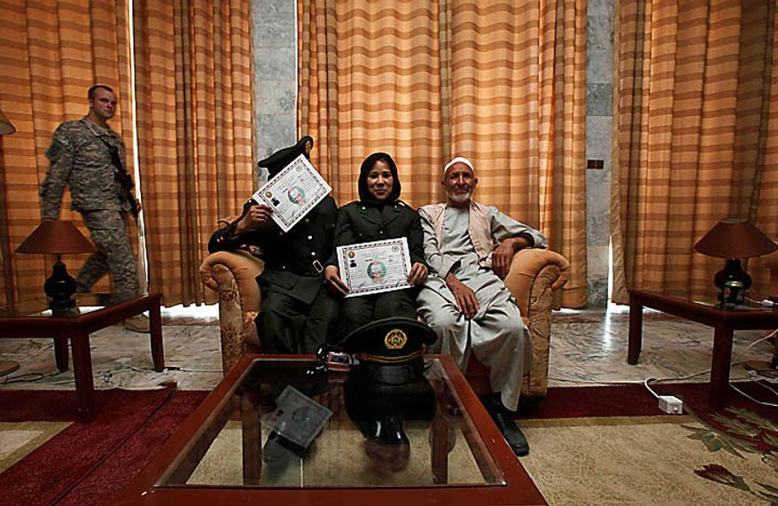 Newly graduated female army officers of Afghan National Army, Zara, center sits with her father, right and fellow officer Safiys after their graduation ceremony at National Army's training center in Kabul, Afghanistan, Thursday Sept. 23, 2010. (AP Photo/ Gemunu Amarasinghe)