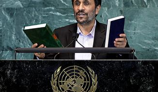 Mahmoud Ahmadinejad, President of Iran, holds up a copies of the Quran, left, and Bible, right, as he addresses the 65th session of the United Nations General Assembly at U.N. headquarters Thursday, Sept. 23, 2010. (AP Photo/Richard Drew)