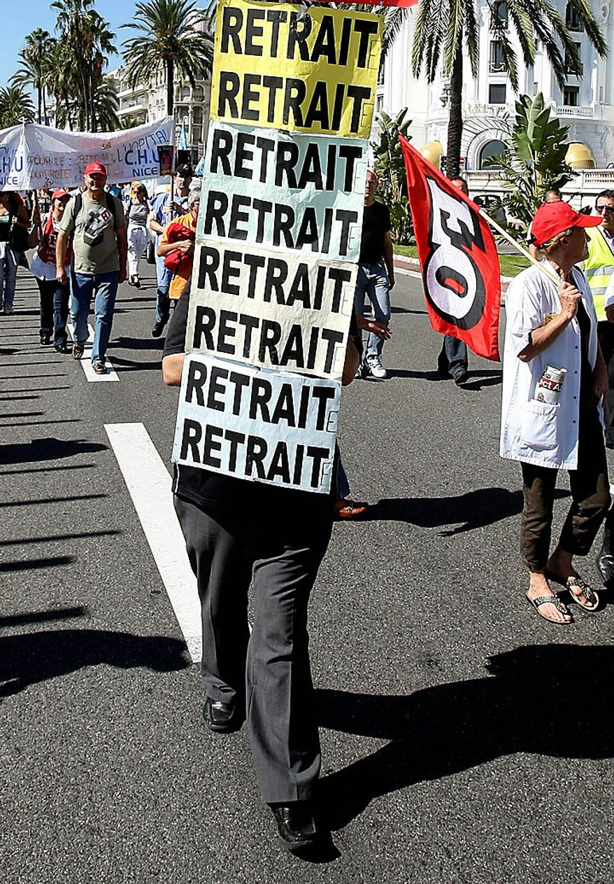 """Workers, one with posters reading """"withdrawal"""" demonstrate in Nice, southern France, Thursday, Sept. 23, 2010. Protesters are counting on people power to pressure the government to back down on its plan to up the retirement age from 60 to 62, with a second round of September strikes expected to hobble public transport, air traffic and schools across France.(AP Photo/Lionel Cironneau)"""