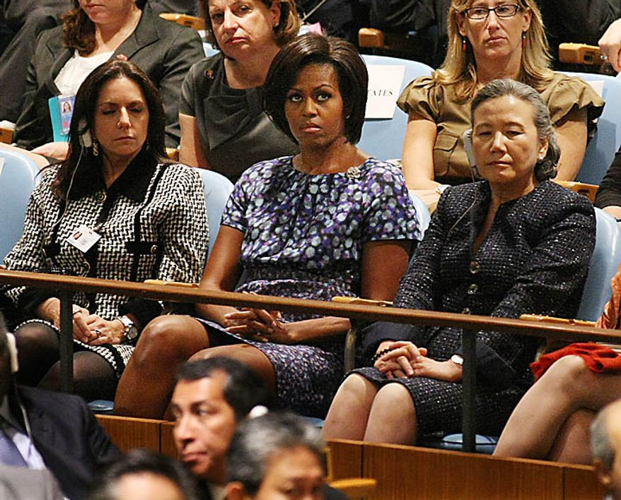 First Lady Michelle Obama, center, listens as her husband U.S. President Barack Obama speaks at the 65th session of the United Nations General Assembly at the UN on September 23, 2010 in New York. ( UPI/Monika Graff )