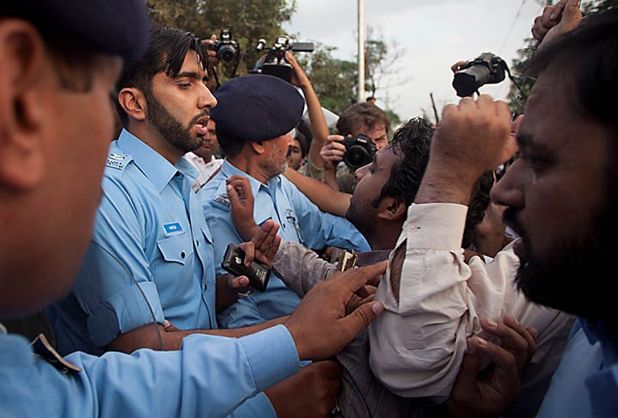 Pakistani police officers block protesters trying to go to the U.S. Embassy in Islamabad, Pakistan, to condemn the sentencing of Aafia Siddiqui on Thursday, Sept. 23, 2010. (AP Photo/B.K. Bangash)