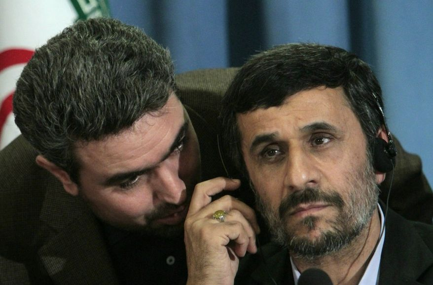 Iranian President Mahmoud Ahmadinejad, right, confers with an aide during a press conference in New York, Friday Sept. 24, 2010. (AP Photo/Bebeto Matthews)