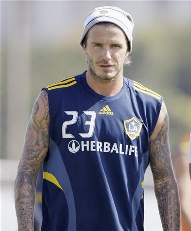 "Los Angeles Galaxy's David Beckham looks on during a soccer training session  in Carson, Calif., Thursday, Sept. 23, 2010. Beckham's management company says it is taking legal action against a U.S. magazine that published claims the former England captain slept with prostitutes. The company says in a statement the allegations in the weekly In Touch are ""completely untrue and totally ridiculous as the magazine was clearly told before publication."" (AP Photo/Reed Saxon)"