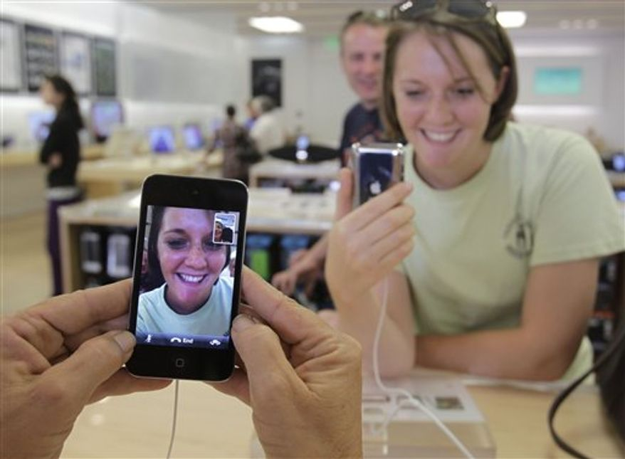 In this Sept. 9, 2010 photo, a customer tests the new Apple iPod Shuffle on display at an Apple Store in Palo Alto, Calif. (AP Photo/Paul Sakuma)