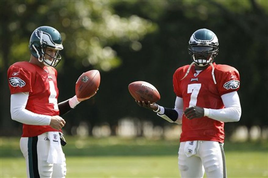 Philadelphia Eagles quarterbacks Michael Vick, right, and Kevin Kolb are seen during practice at the team's NFL football training facility in Philadelphia, Wednesday, Sept. 22, 2010. Vick will take over as the Philadelphia Eagles' No. 1 quarterback, coach Andy Reid said Tuesday, a day after he announced he would go back to Kevin Kolb.  (AP Photo/Matt Rourke)