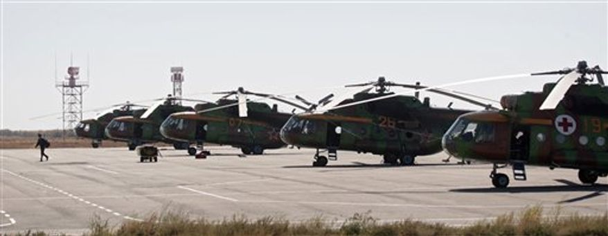 A rescue helicopter stands at the airport of town of Dzhezkazgan, in central Kazakhstan, on Friday, Sept. 24, 2010. The return of two Russian cosmonauts and an U.S. astronaut to Earth from the International Space Station that was scheduled for Friday has been pushed back by a day because of problems encountered while undocking, the head of the Russian space agency said. (AP Photo/Sergei Remezov, Pool)