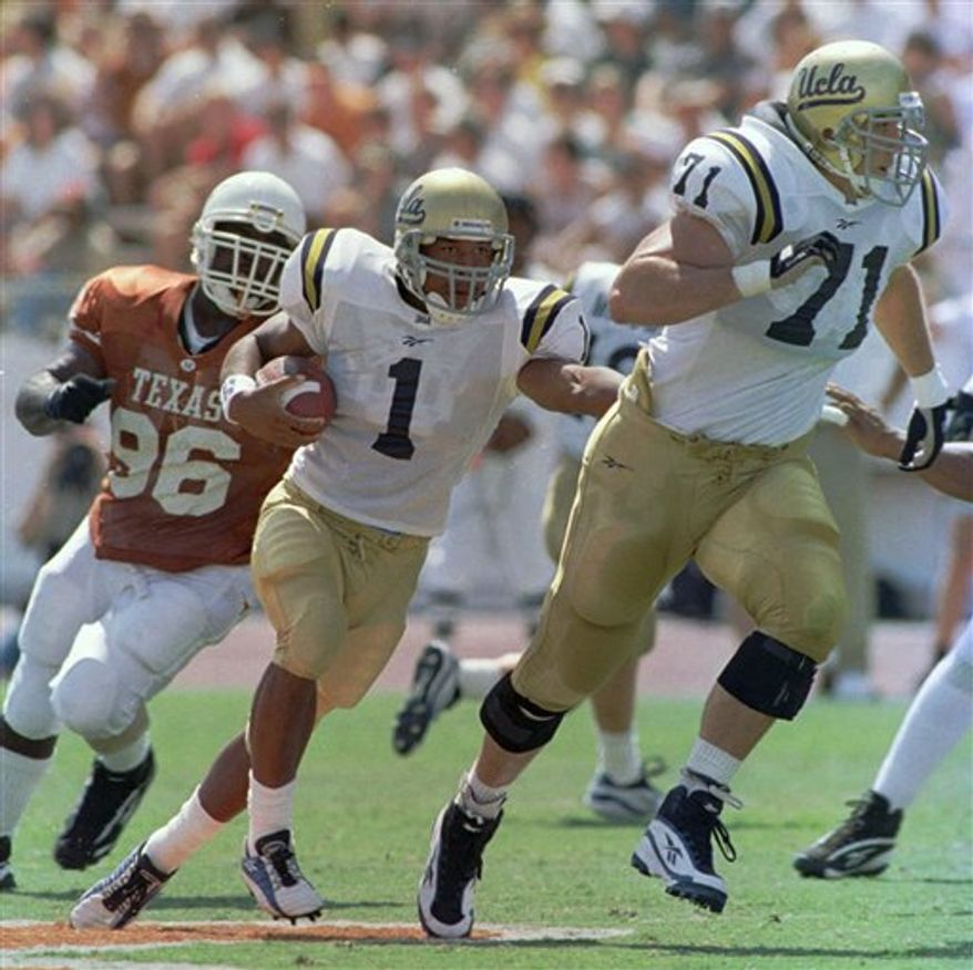 FILE - In this Sept. 13, 1997, file photo, UCLA tailback Keith Brown (1) follows the lead of offensive tackle Kris Farris (71)  for a 29-yard run against Texas during an NCAA college football game in Austin, Texas. Texas defensive tackle Chris Akins is at left. UCLA won 66-3. On Saturday, The Bruins come back to Austin this weekend. The current Longhorns were hardly in grade school in 1997, but fans and former players will always remember the day UCLA jammed a big ol' stick right into the eyes of Texas. (AP Photo/George Bridges, File)