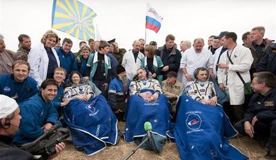 Expedition 24 Flight Engineer Tracy Caldwell Dyson, left, Commander Alexander Skvortsov, center and Mikhail Kornienko sit in chairs outside the Soyuz Capsule just minutes after they landed near the town of Arkalyk, Kazakhstan on Saturday, Sept. 25, 2010.  Russian Cosmonauts Skvortsov and Kornienko and NASA Astronaut Caldwell Dyson, are returning from six months onboard the International Space Station. (AP Photo/NASA - Bill Ingalls)