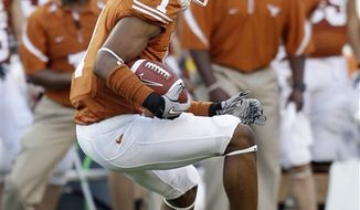 In this photo taken Sept. 11, 2010, Texas freshman wide receiver Mike Davis (1) makes a reception against Wyoming during the first quarter of an NCAA college football game, in Austin, Texas. Texas has a dozen true freshmen on the two-deep depth chart and they are making plays for the No. 7 Longhorns.  (AP Photo/Eric Gay)