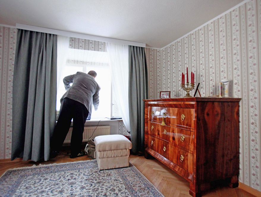 Robert Tidmarsh, who lives in former servant quarters on the grounds of the Schoenbrunn Palace in Vienna, Austria, shuts a window of his apartment. He has lived at Schoenbrunn for about 30 years. (Associated Press)