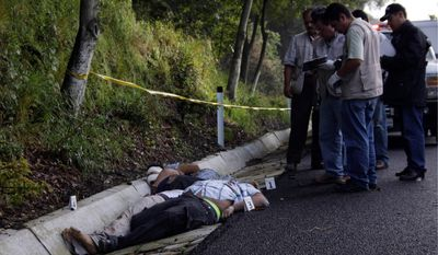 Mexican police investigate where the bodies of four men were dumped Sunday at the side of the Mexico City-Acapulco highway near Cuernavaca. A warning left with the bodies was signed by the Southern Pacific drug cartel. (Associated Press)