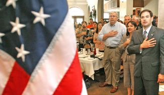 """**FILE** Republican U.S. Senate nominee Marco Rubio takes the Pledge of Allegiance before addressing supporters during a """"Reclaim America"""" town-hall meeting in Longwood, Fla., in 2010. (Associated Press)"""