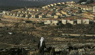 "A Palestinian shepherd walks near the Jewish settlement of Revava, near the West Bank village of Salfit, on Saturday, Sept. 25, 2010. Danny Danon, a pro-settler lawmaker in Prime Minister Benjamin Netanyahu's Likud Party, said on Saturday that settlers already have moved equipment into Revava and that activists would lay the cornerstone for a new neighborhood on Sunday, the last day of the Israeli construction slowdown. The activists planned additional construction Monday after the restrictions formally end. ""Building will begin there tomorrow afternoon and continue there on Monday,"" Mr. Danon said. (AP Photo/Nasser Ishtayeh)"