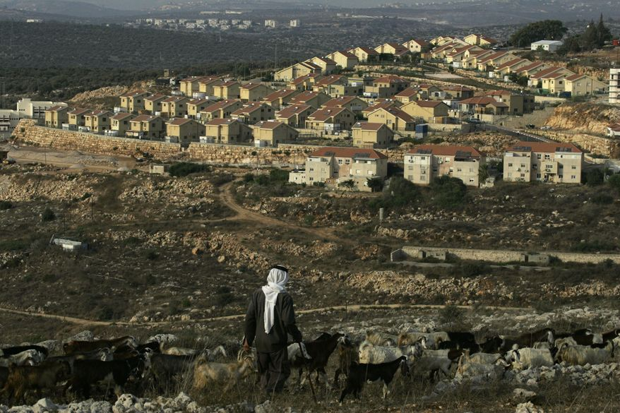 """A Palestinian shepherd walks near the Jewish settlement of Revava, near the West Bank village of Salfit, on Saturday, Sept. 25, 2010. Danny Danon, a pro-settler lawmaker in Prime Minister Benjamin Netanyahu's Likud Party, said on Saturday that settlers already have moved equipment into Revava and that activists would lay the cornerstone for a new neighborhood on Sunday, the last day of the Israeli construction slowdown. The activists planned additional construction Monday after the restrictions formally end. """"Building will begin there tomorrow afternoon and continue there on Monday,"""" Mr. Danon said. (AP Photo/Nasser Ishtayeh)"""