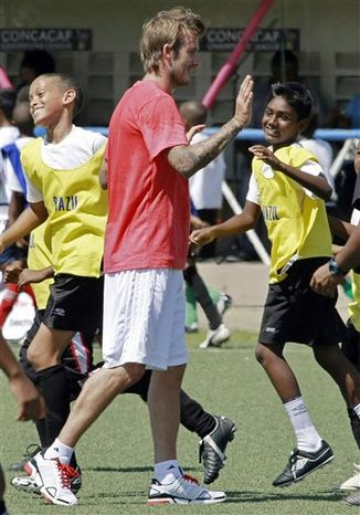David Beckham, former England's soccer team captain and Los Angeles Galaxy midfielder, high fives with young players during a coaching clinic in Macoya, Trinidad and Tobago, Sunday, Sept. 26, 2010. Beckham is visiting Trinidad and Tobago to bolster both England's World Cup bid and Caribbean youth football. (AP Photo/Anthony Harris)
