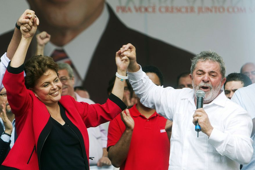 Brazilian President Luiz Inacio Lula da Silva gives a hand to his choice as his successor, Dilma Rousseff, during a campaign rally in Campinas on Sept. 18. (Associated Press)