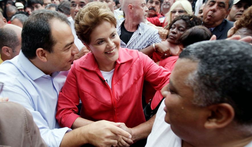 Mrs. Rousseff is joined by Rio de Janeiro Gov. Sergio Cabral in greeting supporters during a campaign rally at Rio's Center of Northeastern Traditions on Sept. 26. Election Day is Oct. 3. (Associated Press)