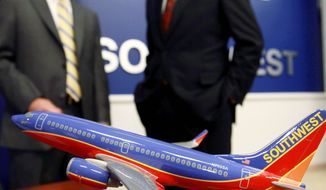 Robert Fornaro, CEO of AirTran Holdings Inc. (left), and Gary Kelly, his counterpart at Southwest Airlines Co., chat after a news conference at Southwest's headquarters in Dallas on Monday. (Bloomberg)