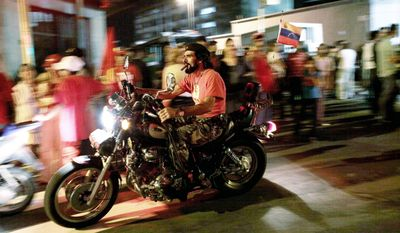 """PASSING FANCY: Posing as Cuban revolutionary """"Che"""" Guevara, a rider passes near the Venezuelan presidential palace. Voters gave a newly unified opposition a significant bloc of National Assembly seats. (Associated Press)"""