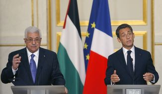 French President Nicolas Sarkozy (right) reacts during a meeting with Palestinian President Mahmoud Abbas at the Elysee Palace on Monday, Sept. 27, 2010, in Paris. Mr. Abbas said Sunday that Israel must choose between peace or settlements as Israel's 10-month settlement construction slowdown expired. (AP Photo/Jacques Brinon)