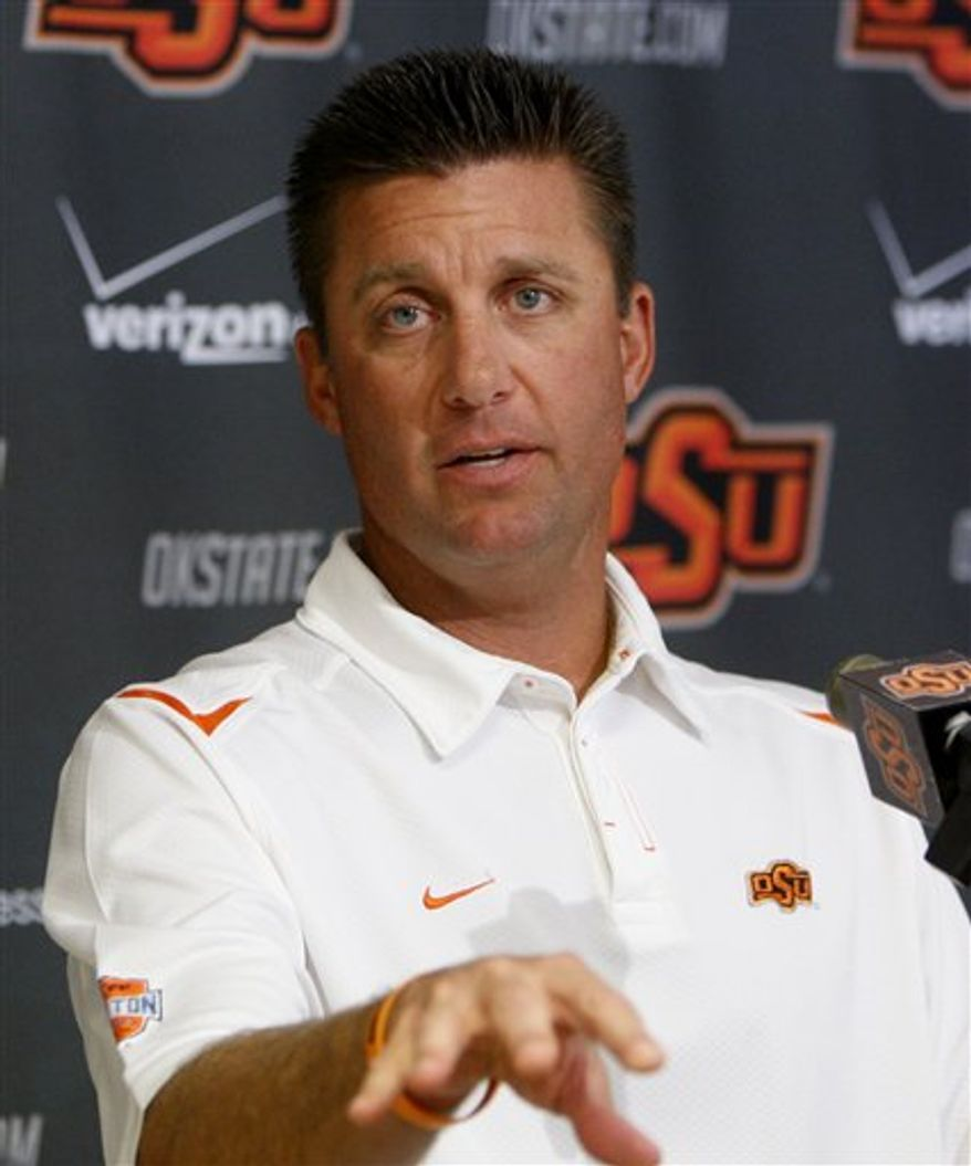 Oklahoma State head coach Mike Gundy gestures as he answers a question during an NCAA college football news conference in Stillwater, Okla., Thursday, Sept. 23, 2010, 2010. An off week will give Oklahoma State's players a chance to relax and catch up on school work and coaches a couple days to hit the recruiting trail. (AP Photo/Sue Ogrocki)