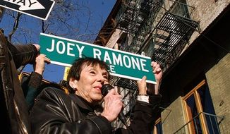 FILe - In this Nov. 30, 2003 file photo, Charlotte Lesher, the mother of Ramones singer Joey Ramone, holds a sign that honors her son in New York, and names the corner of Bowery and 2nd Street Joey Ramone Place, in honor of the punk musician. (AP Photo/Gregory Bull, file)