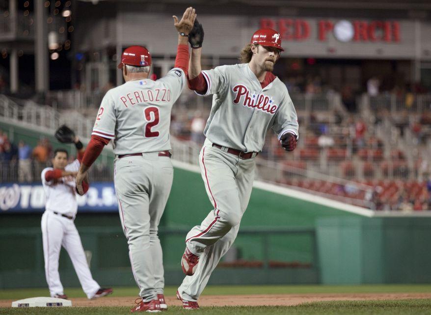 ASSOCIATED PRESS Washington Nationals third baseman Alberto Gonzalez, left, looks on as Philadelphia Phillies  third base coach Sam Perlozzo congratulates Jayson Werth for hitting a solo home run during the second inning of a baseball game Monday, Sept. 27, 2010, in Washington.